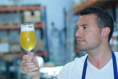 the brewer: brewer testing beer at brewery