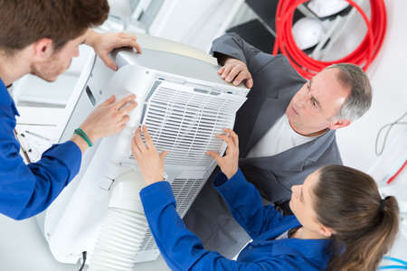 class maintenance: Young people woking on air conditioning unit Stock Photo
