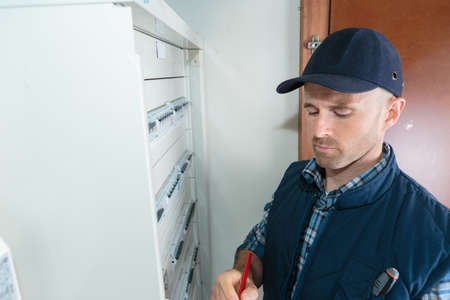 male technician writing on clipboard in front of fusebox