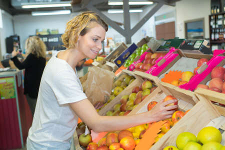 attractive woman choosing fruits in grocery store