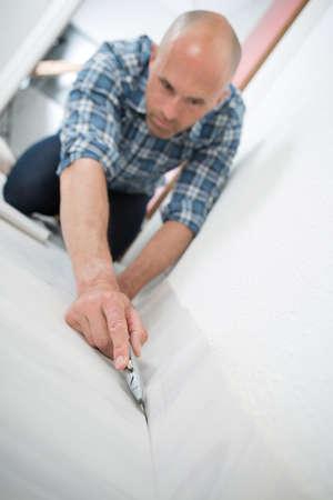 close-up of a handyman cutting floor Stock Photo