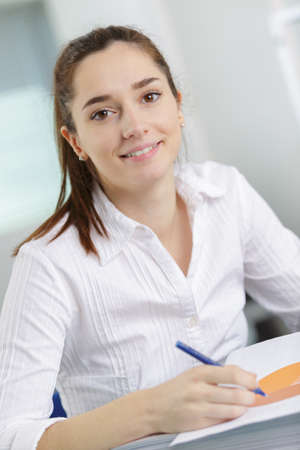 make summary: portrait of a female student at workplace studying