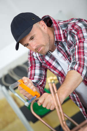 plumber cutting copper pipe Stock Photo
