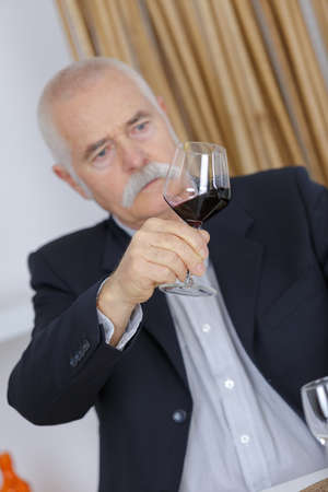 satisfied mature man holds a red wine glass