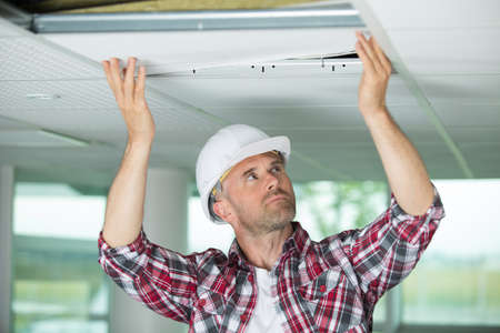Contractor replacing ceiling panel