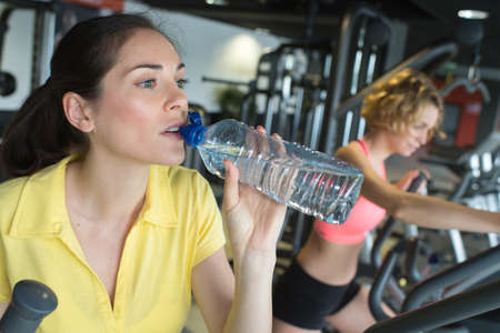 beautiful girl drinking water in the gym after long training Stock Photo