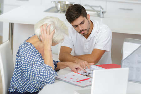 afflictions: photo of young man helping his grandmother managing her money Stock Photo