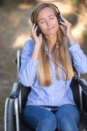 young disabled woman relaxing with music in nature