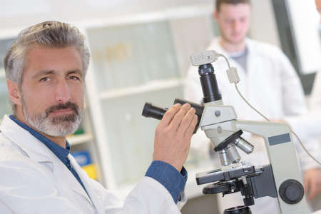 scientist examining sample with microscope in the laboratory Stock Photo