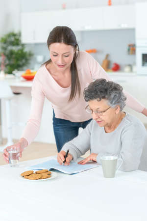 the grand daughter: grandmother solving crosswords puzzle helped help by her grand daughter Stock Photo