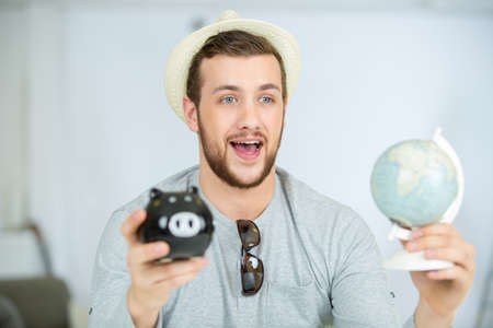 to drown: happy man holding piggy bank and globe
