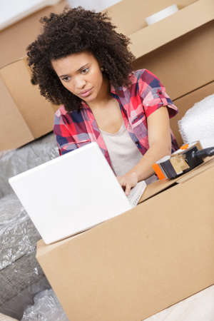 homeoffice: beautiful woman working with a laptop during office relocation