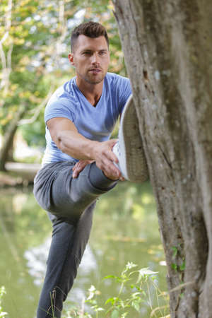 young man doing stretching against a tree in a park Stock Photo