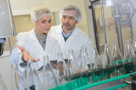 Portrait of two positive workers at bottling company factory