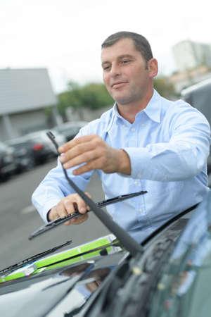man die nieuw wisserblad op zijn auto zet Stockfoto