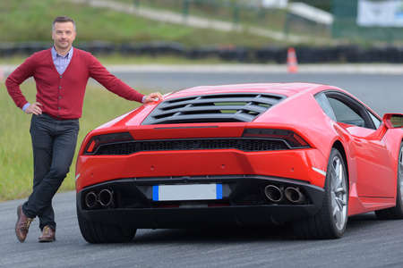 smiling man posing against red sport car on a circuit