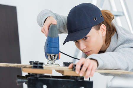 cutting: female carpenter using bandsaw