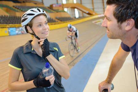 additional training: female athlete talking with coach on the velodrome track