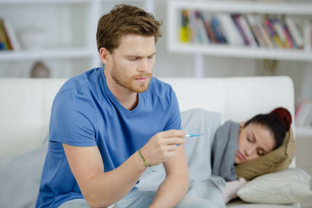 sick woman with boyfriend monitoring her temperature with thermometer