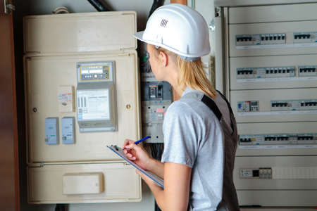 electrician woman solving problem on electrical board