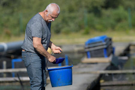communications tools: old man holding bucket at fish farm Stock Photo