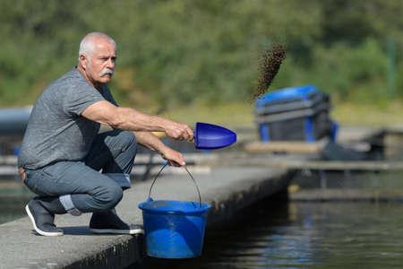 Mannelijke visboer die vis voedt Stockfoto