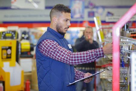 Lavoratore che controlla il prodotto nel negozio