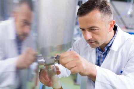 맥주에서 맥주 병을 작성하는 맥주 양조업자의 근접 스톡 콘텐츠
