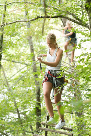 cute girl climbing in the trees at adventure park Stock Photo
