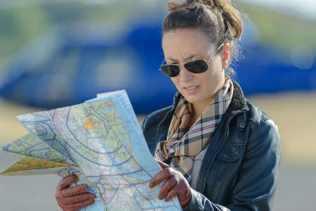 young woman helicopter pilot reading map Stock Photo - 82452720