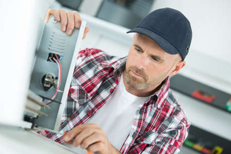 young repairer working with screwdriver in service center Stock Photo