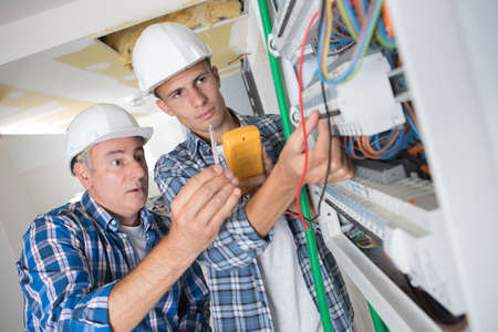 young apprentice with electrician professional 写真素材