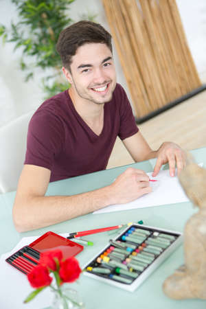 young man drawing pictures in studio Stock Photo