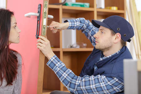 cheerful locksmith installing a door lock under clients surveillance Standard-Bild