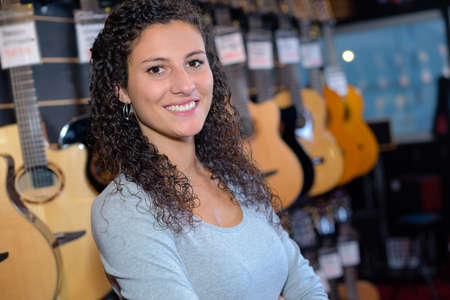 portrait of woman seller in guitar shop