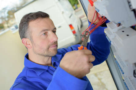 electrician cuts wire with pliers Stock Photo