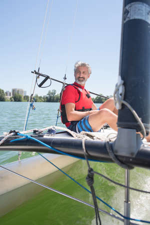handsome mature man sailing on a lake