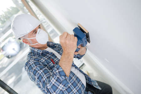aged builder in hardhat sanding wall indoors