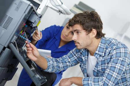 two young technicians repairing printer 版權商用圖片