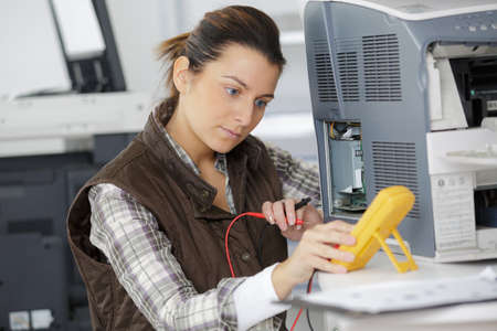 handywoman checking computer with a multimeter