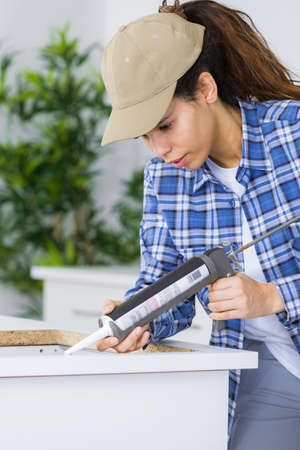 woman builder with caulking gun working in clients kitchen Stock fotó
