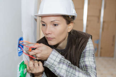 female electrician inspecting the wires