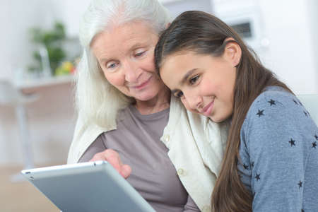 happy grandmother with grand daughter looking at a tablet
