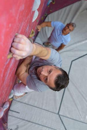 magnesia: free climber young man climbing artificial boulder indoors Stock Photo