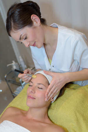 close-up of a relaxed woman receiving therapy on forehead