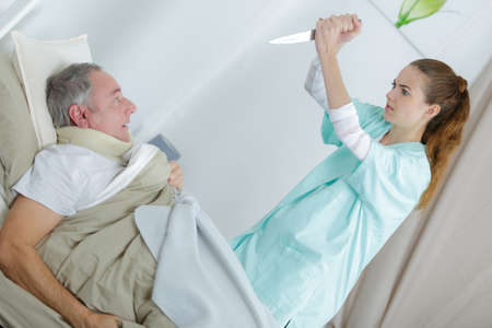 crazy nurse wielding knife to kill a patient Stock Photo