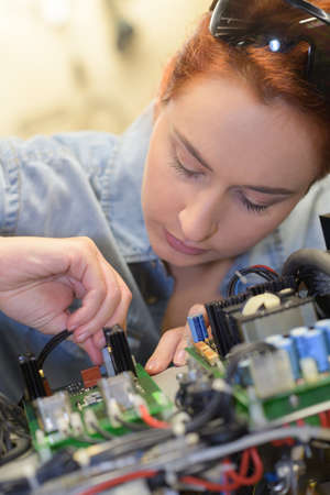 girl wiorking on a printed circuit board Stock Photo