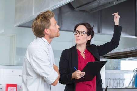 pretty female inspector examining restaurant kitchen with young chef
