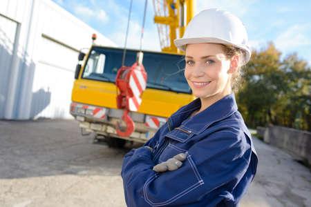 vrouwelijke ingenieur die zich voor kraanvrachtwagen bevindt Stockfoto