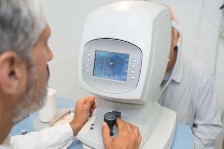 attentive optometrist examining male patient on machine Reklamní fotografie
